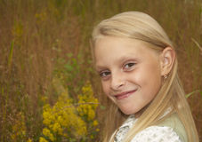 Girl in the field. A small blond girl in the field royalty free stock image