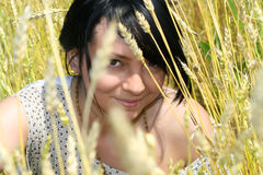 Girl in a field. Looking out for the ripe ears of wheat Royalty Free Stock Images
