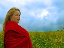 Girl in field. A young blond girl wrapped in red blanket standing in a yellow plants field stock photos