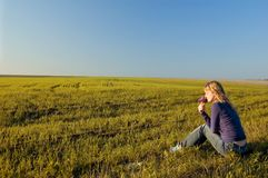 Girl in the field. Girl sits on a grass against an autumn landscape Stock Images