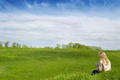 Girl in the field. Girl sits on a grass and hold look far away Stock Photos