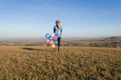 Girl on the field with balloons. Girl on the field holding balloons Stock Photography