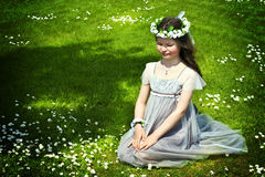 Girl on the field. Beautiful girl sitting on the grass in the park Stock Photo