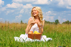 Girl in a field. Beautiful smiling blonde with a basket of fruit royalty free stock photos