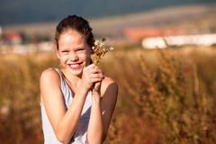 Girl on the field. Beautiful, 11 years old girl in the field, smiling and holding some flowers Royalty Free Stock Photo