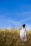 Beautiful, graceful,posing girl stand in field with blue sky. stock photography