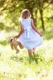 Girl In Field Carrying Teddy Bear. Young Girl Walking Through Summer Field Carrying Teddy Bear Royalty Free Stock Images