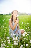 Girl on field with dandelion Royalty Free Stock Photos