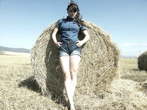 Woman in denim costume in the straw field Royalty Free Stock Image