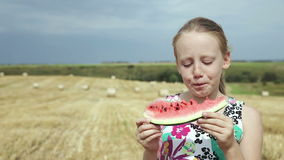 Girl in a field eating watermelon stock footage