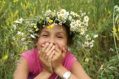 Girl in field flower garland. Cheerful preteen girl in field flower garland on green grass background Stock Photos