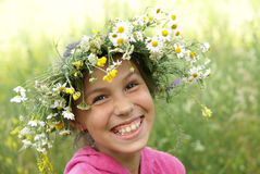 Girl in field flower garland Royalty Free Stock Image