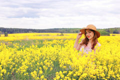 Girl in a field of flowers with basket and a hat Stock Image