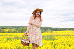 Girl in a field of flowers with basket and a hat Royalty Free Stock Photos