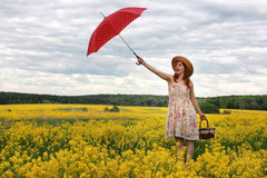Girl in a field of flowers with an umbrella and a hat Royalty Free Stock Image