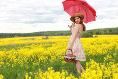 Girl in a field of flowers with an umbrella and a hat Stock Photos