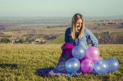 Girl on the field holding  balloons. Girl on the green field holding colorfull balloons Royalty Free Stock Photography