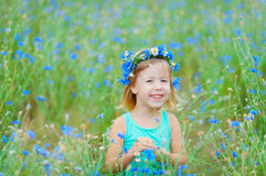 Girl in a field holding a bouquet of blue flowers Royalty Free Stock Photos