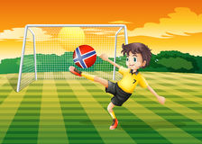 A girl at the field kicking the ball with the flag of Norway Stock Images