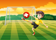 A girl at the field kicking the ball with the flag of Switzerlan Royalty Free Stock Photo