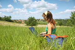 Girl in field with laptop Royalty Free Stock Image