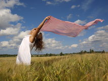 Girl in a field with a pink scarf Stock Image