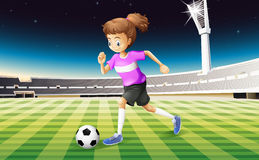 A girl at the field playing football Stock Photo