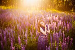 Girl in field of purple wildflowers, sunset on Sunny day. Beautiful girl in a field of purple wildflowers at sunset on a Sunny day Stock Photos