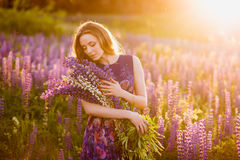 Girl in field of purple wildflowers, sunset on Sunny day Royalty Free Stock Photo