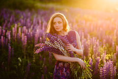 Girl in field of purple wildflowers, sunset on Sunny day Stock Photography