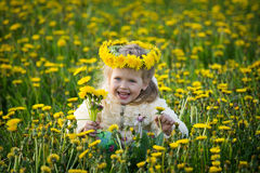 The girl in the field. The small laughing girl in the field with dandelions in a wreath Royalty Free Stock Images