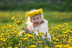 The girl in the field. The small laughing girl in the field with dandelions in a wreath Stock Photography