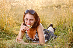 Girl in field smelling flower Royalty Free Stock Photos