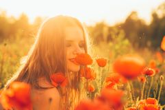 Girl in the field sniffing poppy flower royalty free stock photo