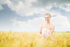 Girl in a field with spikelets. In the sunning day Royalty Free Stock Image