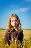 Girl in a field of wheat. Tween aged girl outdoors in a golden field of wheat with a beautiful blue sky Stock Photography