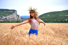 The girl on a field with wheat ears. Girl with a wreath of wheat ears enjoying the sun on the wheat field Stock Photos