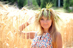 The girl on a field with wheat ears. Girl with a wreath of wheat ears sitting on the field Stock Photo
