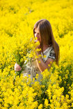 Girl in the field of yellow flowers Stock Images
