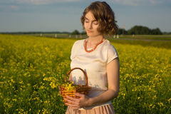 Girl in a field. Young girl standing in a field with a basket in her hand Royalty Free Stock Images