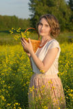 Girl in a field. Young girl standing in a field with a basket in her hand Royalty Free Stock Photography
