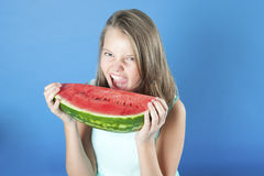 Girl fiercely biting a piece of watermelon. 