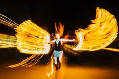 Woman juggles with fire in total darkness Stock Photography