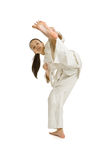 The girl-fighter puts a kick left. The girl-fighter aikido puts a kick left Stock Photo