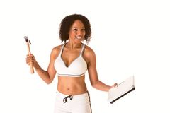 Girl fighting for weight loss. Ethnic woman in sporty outfit hits weight scales by hammer Royalty Free Stock Image