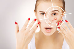 Girl fights ugly skin, grey gradient background. Young broun eyed blond model fights with pimples,target on her face royalty free stock photography