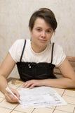 Girl fills accounts Royalty Free Stock Image