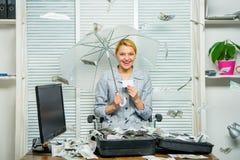 girl financiero lleva a cabo un paquete de placer de los dólares Contable con el dinero de la pila ocultar debajo del paraguas El fotos de archivo libres de regalías