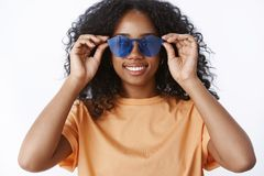 Girl find perfect pair sunglasses make fuss campus. Charming african american female student put eyewear touching frames royalty free stock image