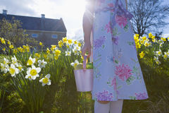 Girl finding chocolate Easter eggs in flowers Royalty Free Stock Image